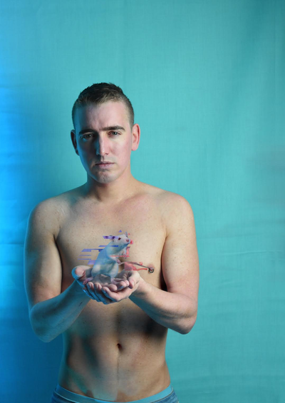 A person standing shirtless holding a mouse which is glitching like a computer, it is an image for I Am B-19, part of the Dublin Gay Theatre Festival 2020