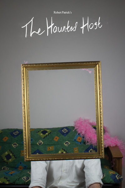 A person sitting behind an empty picture frame, a still from the Haunted Host
